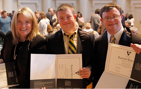 Photo of three young adults with Down syndrome graduating and holding degrees