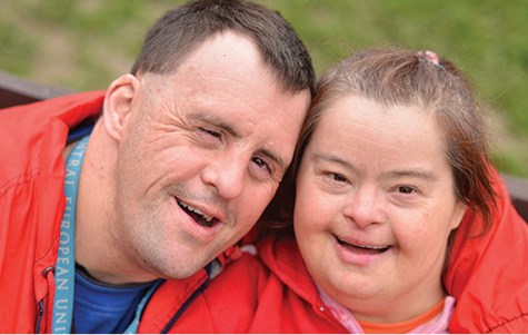 Photo of two happy adult with Down syndrome outside