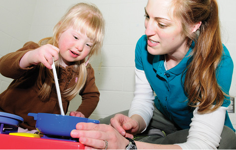 A research assistant works with a young child with Down syndrome.