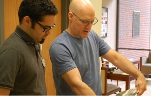 Preston Vienneau (left) working with Lain York (right) to hang art exhibit