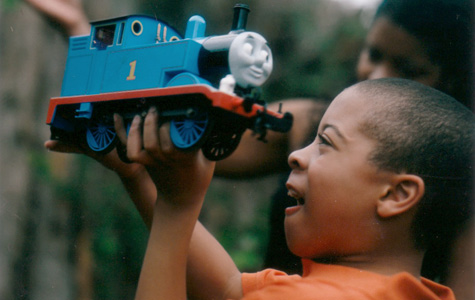 Young boy playing with toy train
