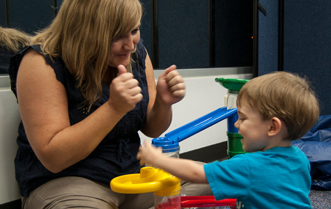 Photo of woman playing with young boy.