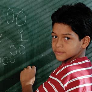 Photo of hispanic boy doing a math problem on a chalkboard