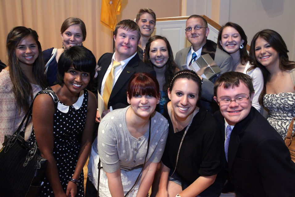 Vanderbilt University students surrounding two students with Down syndrome after graduation