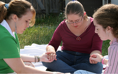 Three teen girls gathered outdoors to pray.