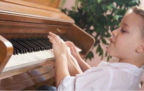 Stock photo of boy playing piano (©2014 Microsoft Corporation)