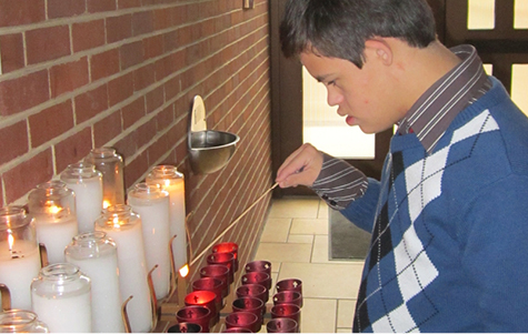 Photo of young adult with Down syndrome lighting candle