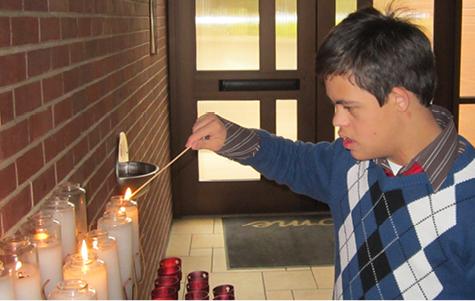 Young man lighting prayer candle