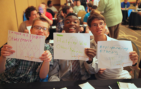 Three boys holding up signs with job interests