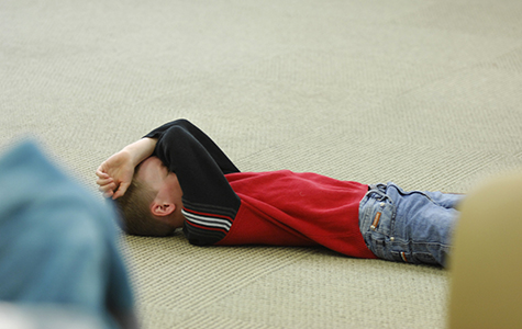 Child Lying on the floow, head covered.