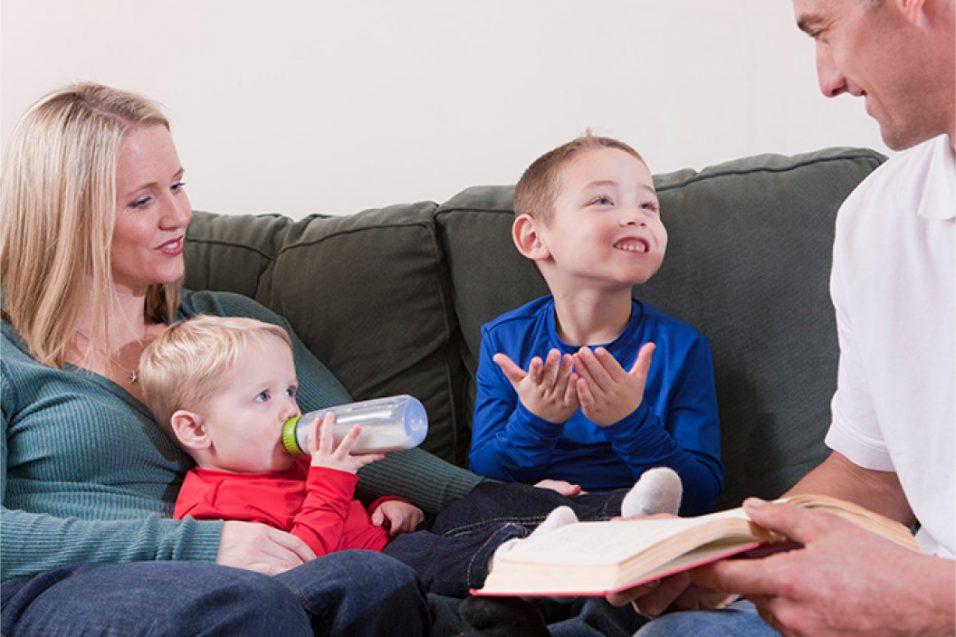young boy using sign language with family