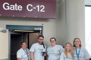 SENSE lab members smiling at airport gate C-12