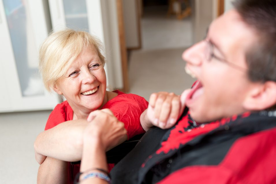 man in wheelchair laughing with woman